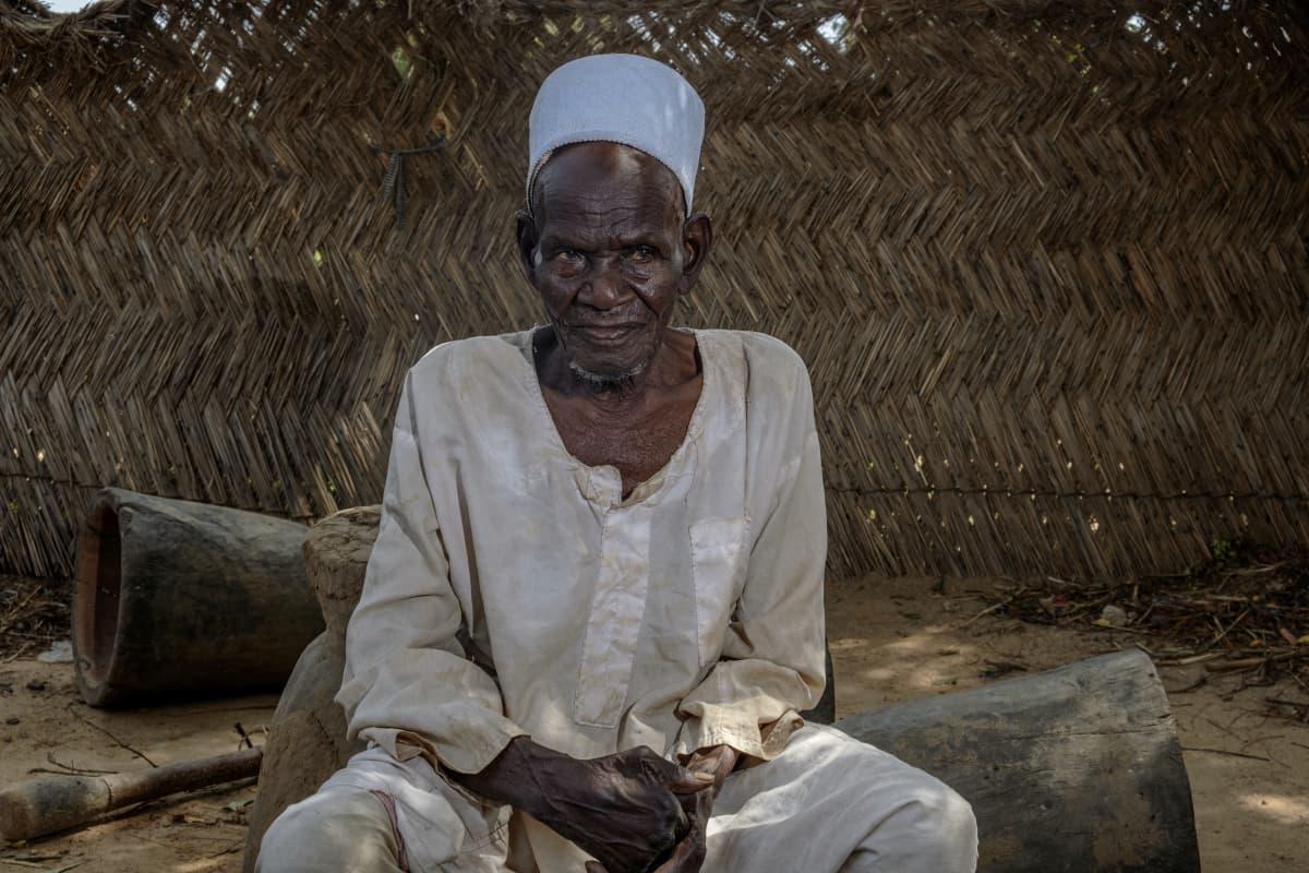 Vanha mies istuu nigeriläiskylässä.