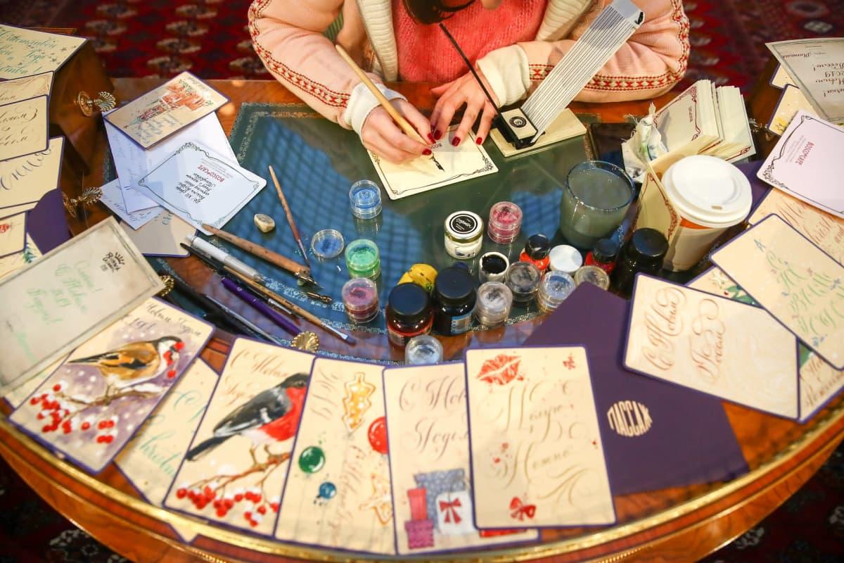 Nainen kirjoittaa joulukortteja