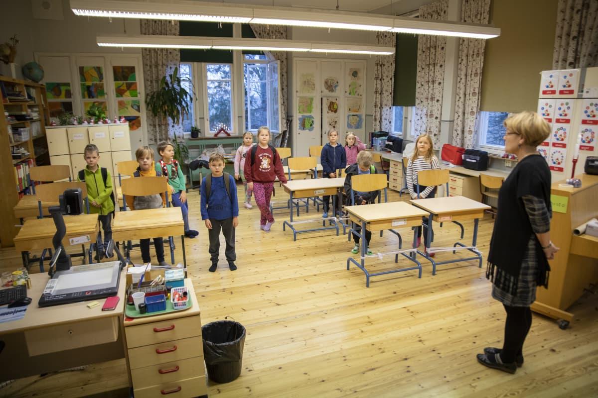 Hajalan koulun 1.-2.-luokkalaiset seisovat luokassa pulpettien vieressä Hajalan koulussa.