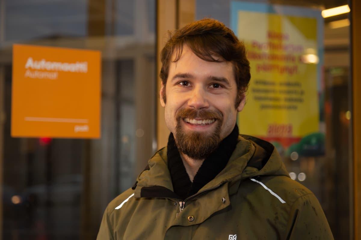Tuomas Finne hymyilee Elävän musiikin yhdistyksen mahdollisen tulevan uuden kodin edessä kauppakeskus Puhoksen pihalla.