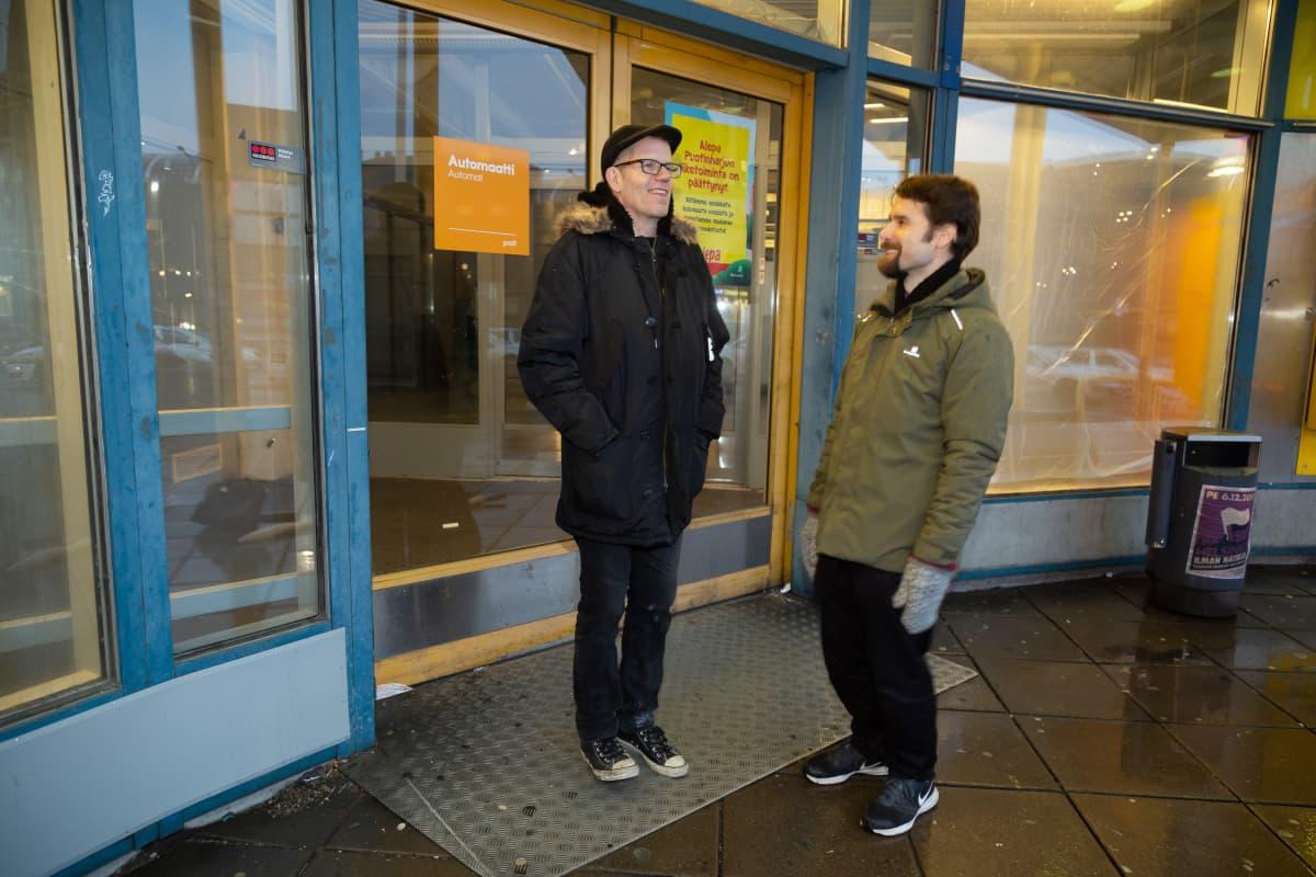 Elmy ry:n johtaja Tapio Hopponen ja aktiivi Tuomas Finne seisovat iloisina kauppakeskus Puhkoksessa toimintansa lopettaneen Alepan ovien edessä. Takana sisällä liiketilassa on pimeää. Ovessa on jäljellä postin automaatista kertova tarra.
