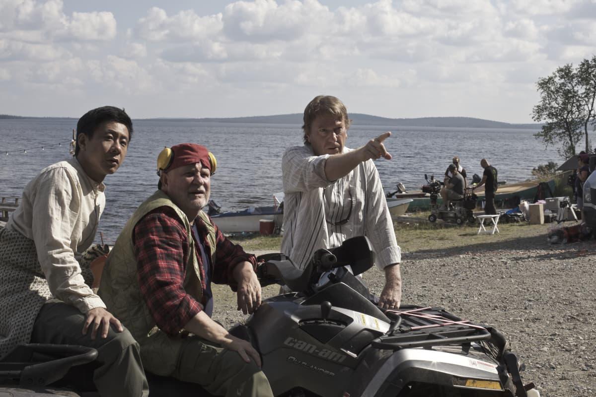 Mika Kaurismäki ohjaa moottoripyörän päällä istuvia Kari Väänästä ja Chu Pak Hongia järven edessä Lapissa.