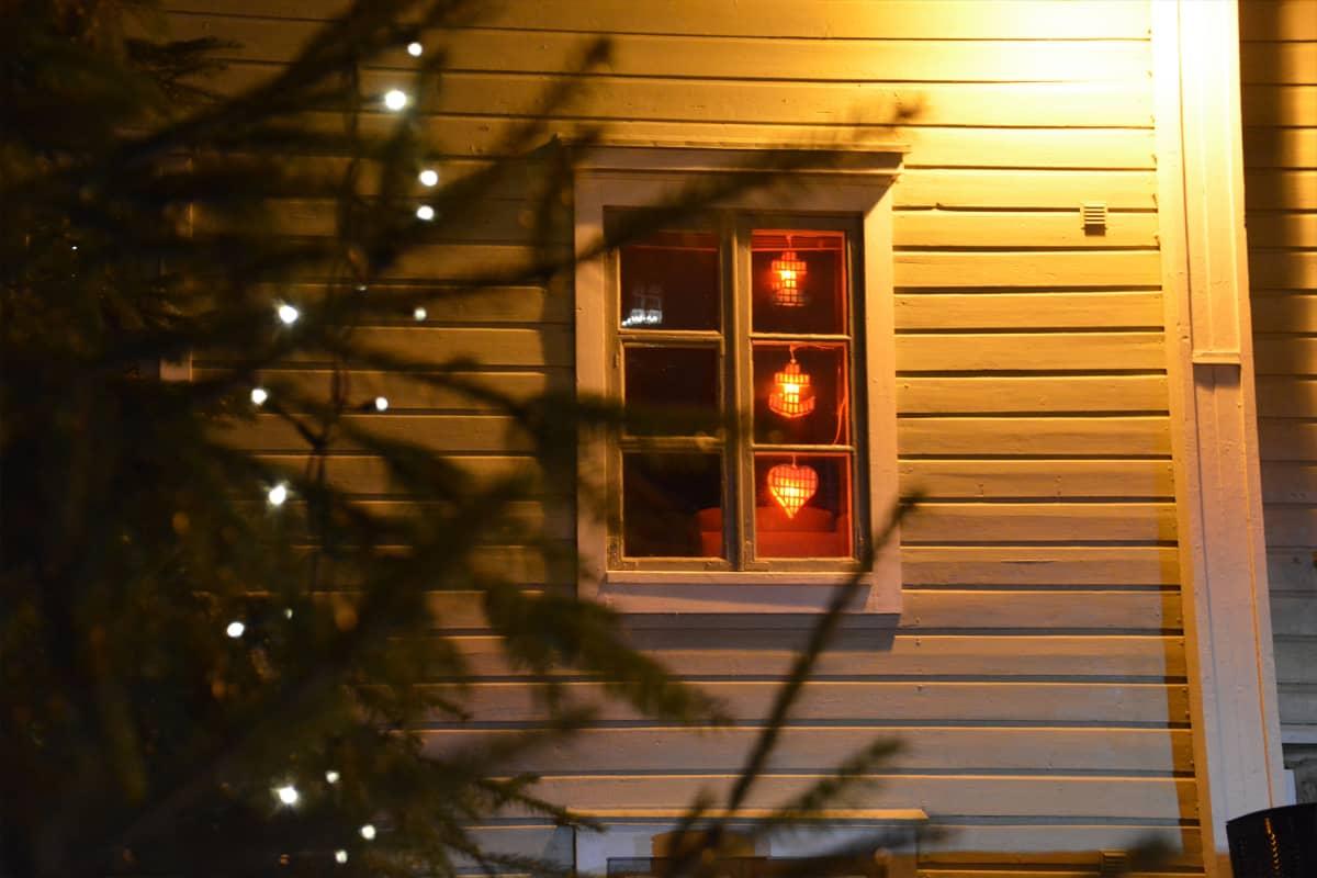 I ett fönster hänger tre röda juldekorationer: ett kors, ett ankare och ett hjärta. Utanför huset, framför fönstret, skymtar en julgran med belysning. Det är mörkt ute men en lampa lyser upp bilden.