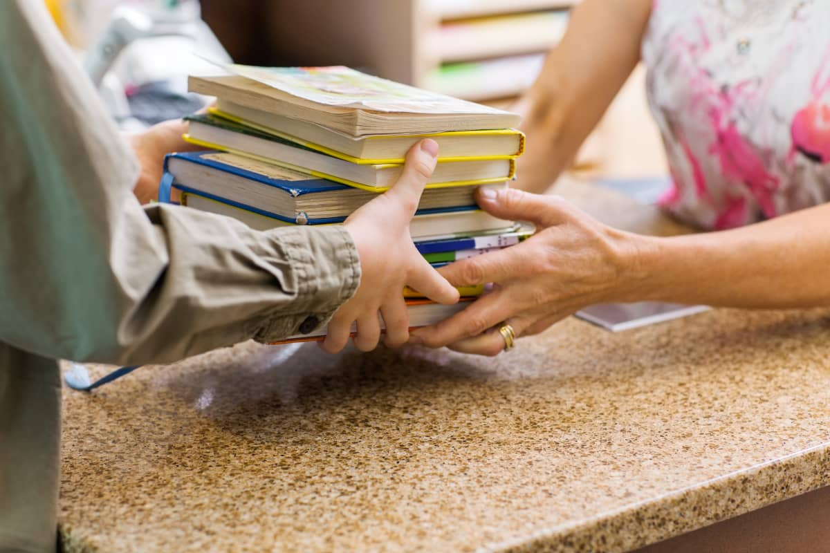 Person räcker över hög med böcker åt en annan person över biblioteksdisk