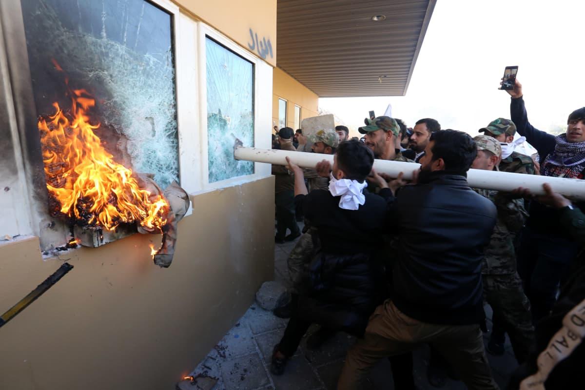 Väkijoukko rikkoo ikkunoita tangolla. Ikkunasta näkyy liekkejä.