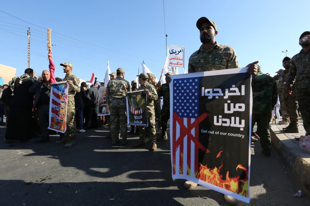 Maastopukuiset miehet pitelevät Yhdysvaltoja vastustavia julisteita.