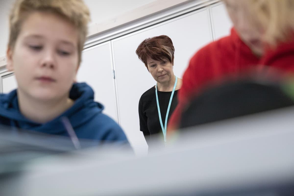 Opettaja katsoo oppilaiden töitä.