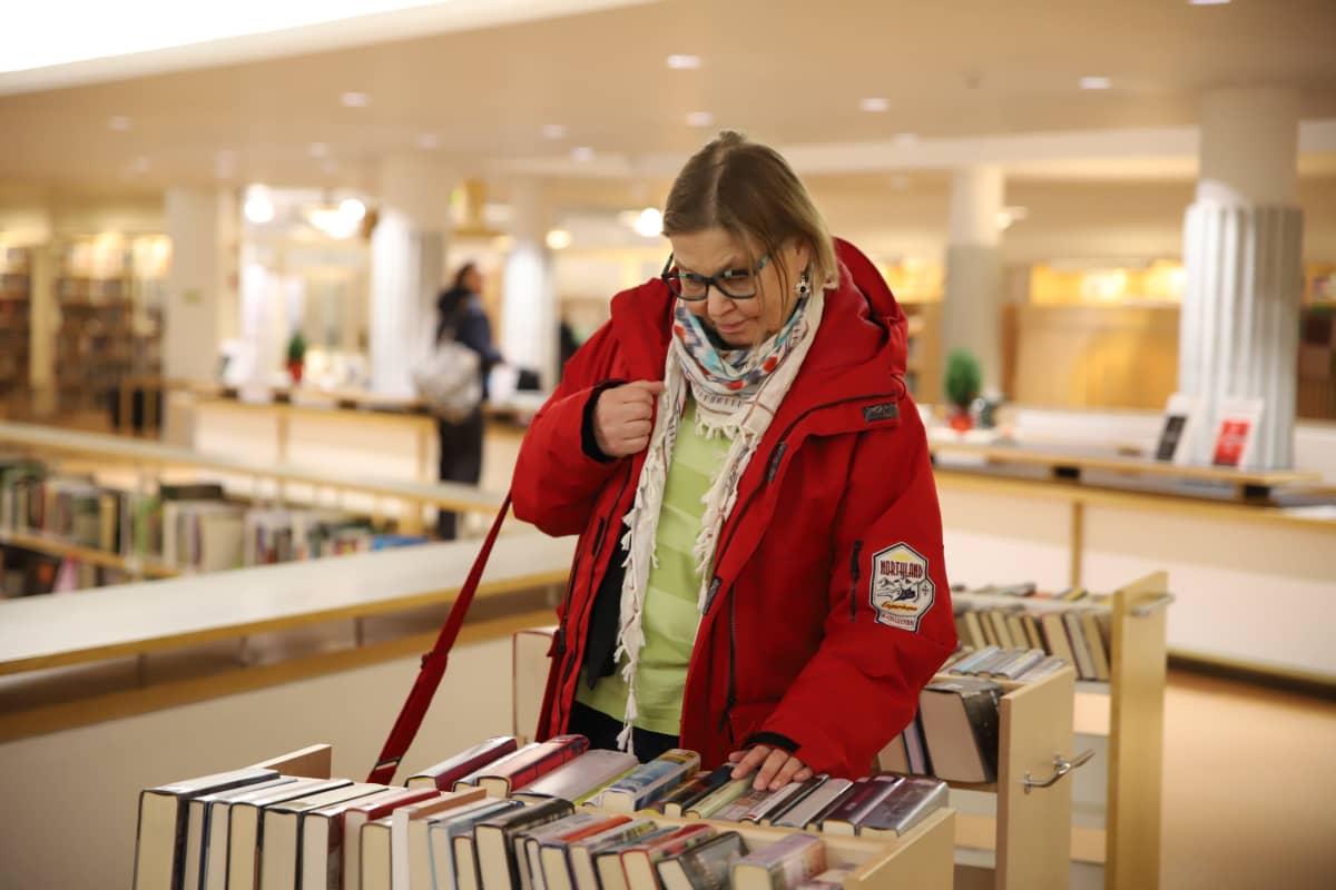 Asta Mommo tutkii kirjavaunun tarjontaa Rovaniemen kirjastossa.