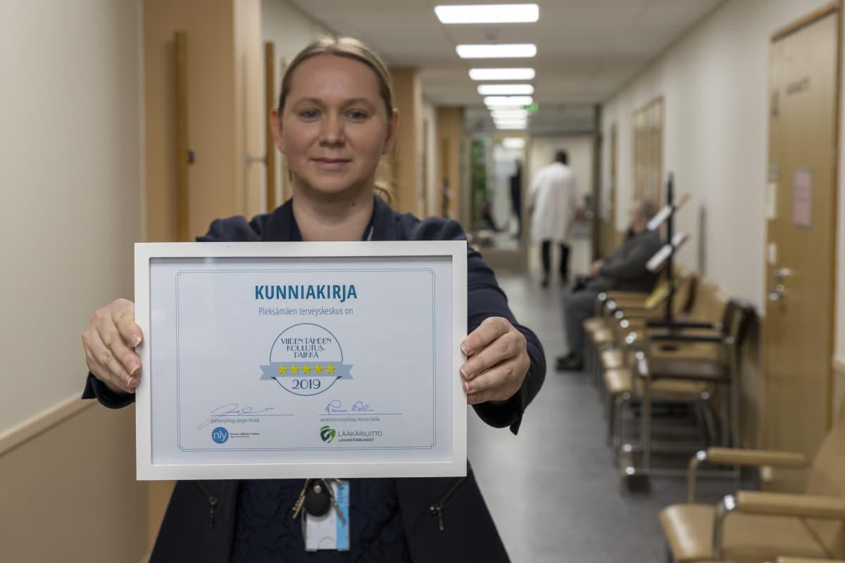 Pieksämäen sairaalan johtava ylilääkäri Aino Rubini näyttää sairaalalle myönnettyä kunniakirjaa. Siinä lukee: Pieksämäen terveyskeskus on viiden tähden koulutuspaikka.