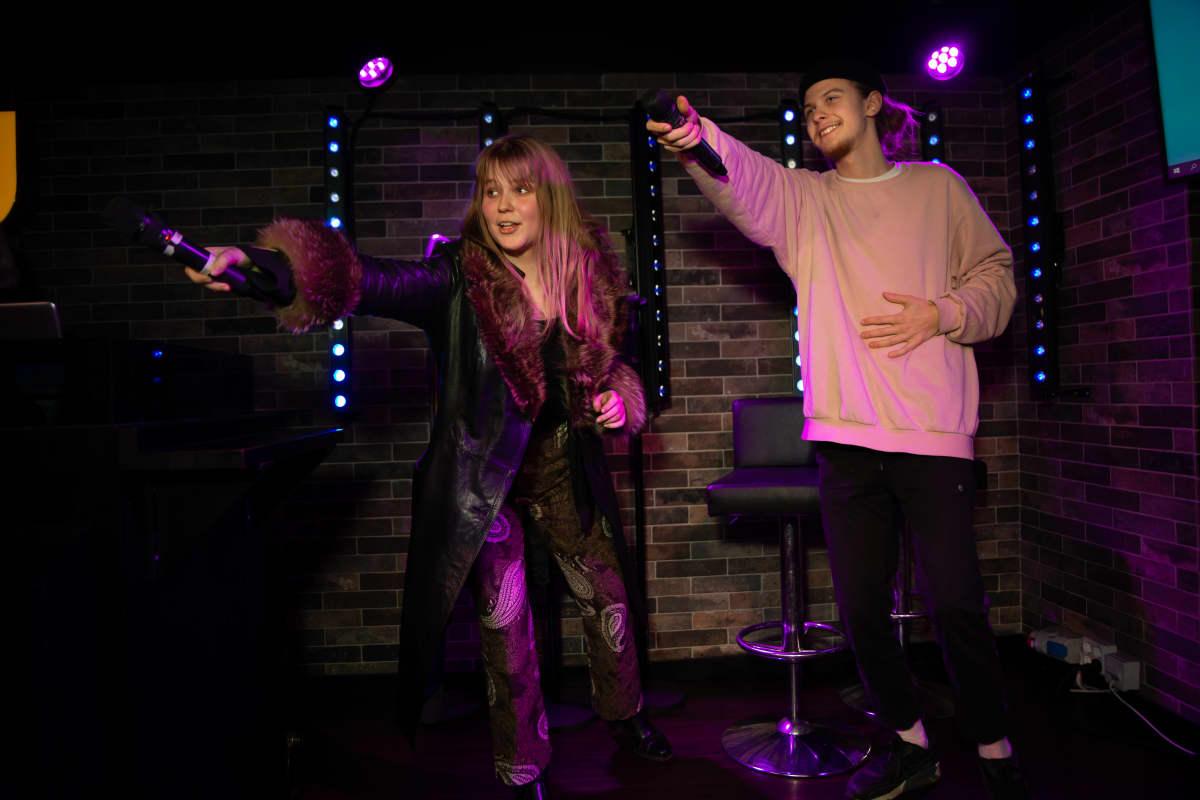 Anna Niemelä ja Olavi Tanttu laulavat karaokea. Kappaleessa on kertosäe meneillään ja laulajat osoittavat mikrofoneillaan kohti yleisöä kannustaen osallistumaan lauluun.