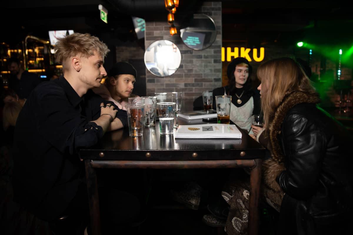 Olavi Tanttu, Arttu Porkka ja Anna Niemelä istuvat pöydän ääressä karaokebaarissa. Pöydällä on tuoppeja joissa vettä ja olutta sekä karaokekappaleiden kataloogi.