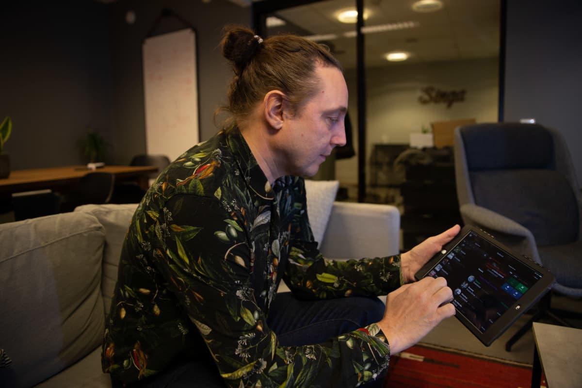 Singa yhtiön Luca Gargano istuu toimistossa sohvalla ja pitää kädessään  tietokonetablettia selaten sillä Singa karaokeohjelman luetteloa musiikkikappaleista.