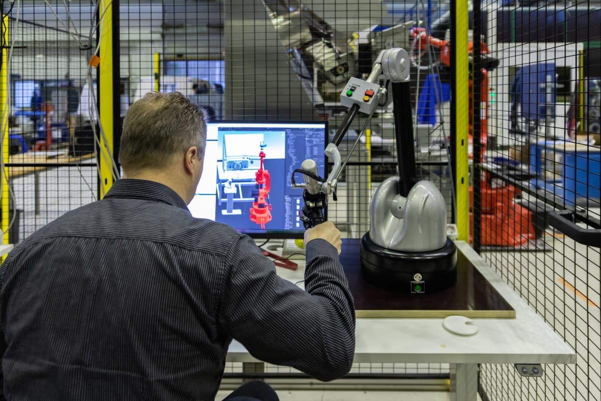 Etäohjauslaitetta kehittävä tutkija työssään VTT:llä Tampereella