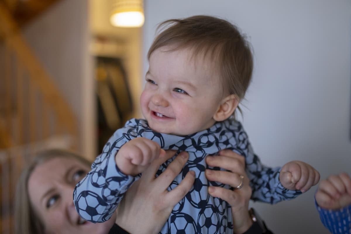 Äiti Henna Kapulainen nostaa poikansa Leon ilmaan.