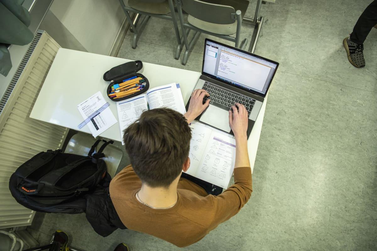 Opiskelija opiskelemassa matematiikkaa.