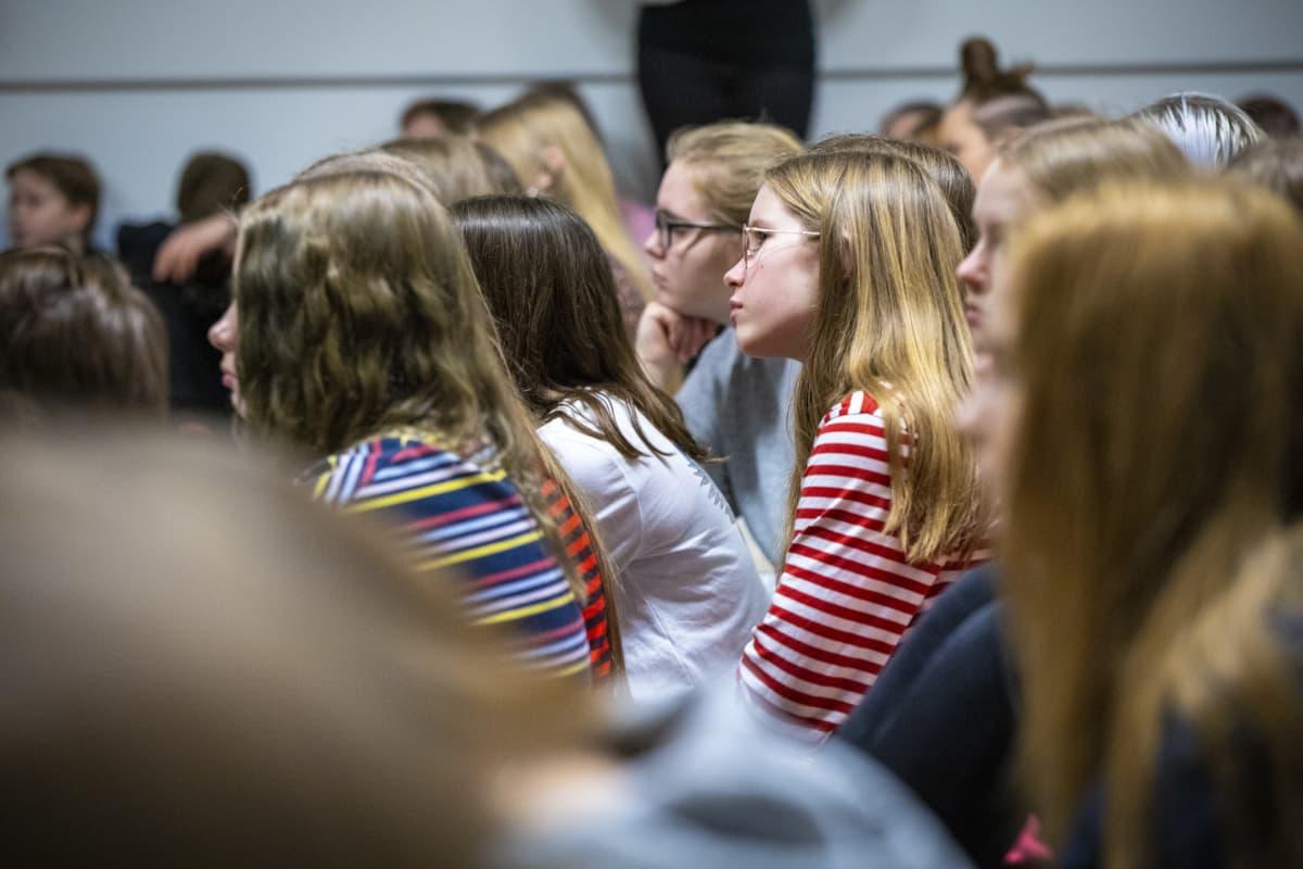 Oppilaita kuuntelemassa Jyri Paretskoita Minna Canthin koulun liikuntasalissa