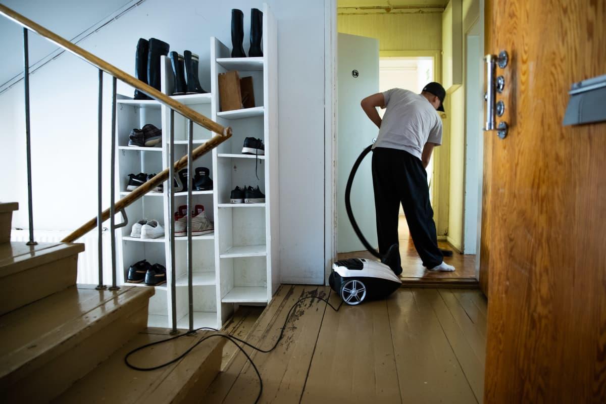 Anonyymi päihdekuntoutuja siivoamassa majoitustiloja