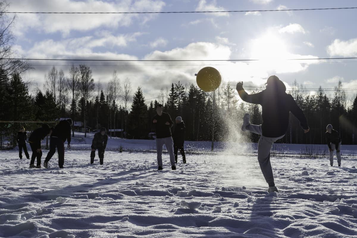 Anonyymit päihdekuntoutujat pelaamassa hankijalkapalloa