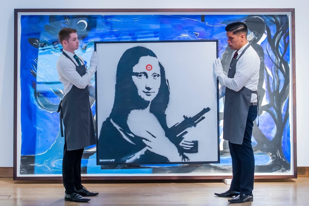Kaksi miestä pitelee Banksyn Mona Lisa -teosta.