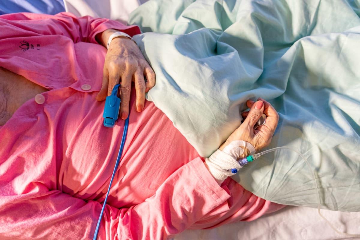 Saturaatiomittari sormessa ja kanyyli käsivarressa iäkkäällä potilaalla.