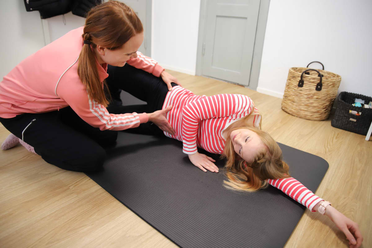 Äitiysfysioterapeutti opastaa asiakasta liikkeen tekemisessä