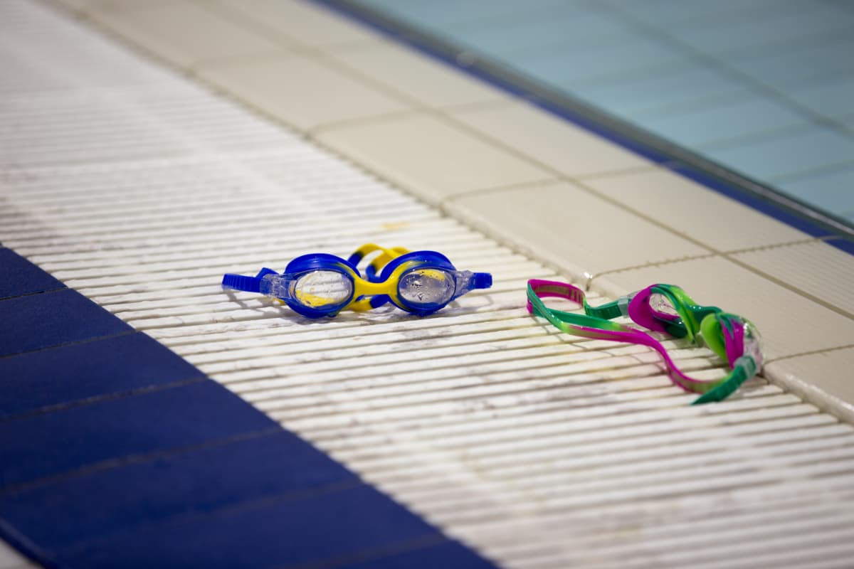 Färgglada simglasögon ligger på kanten till en bassäng i simhallen