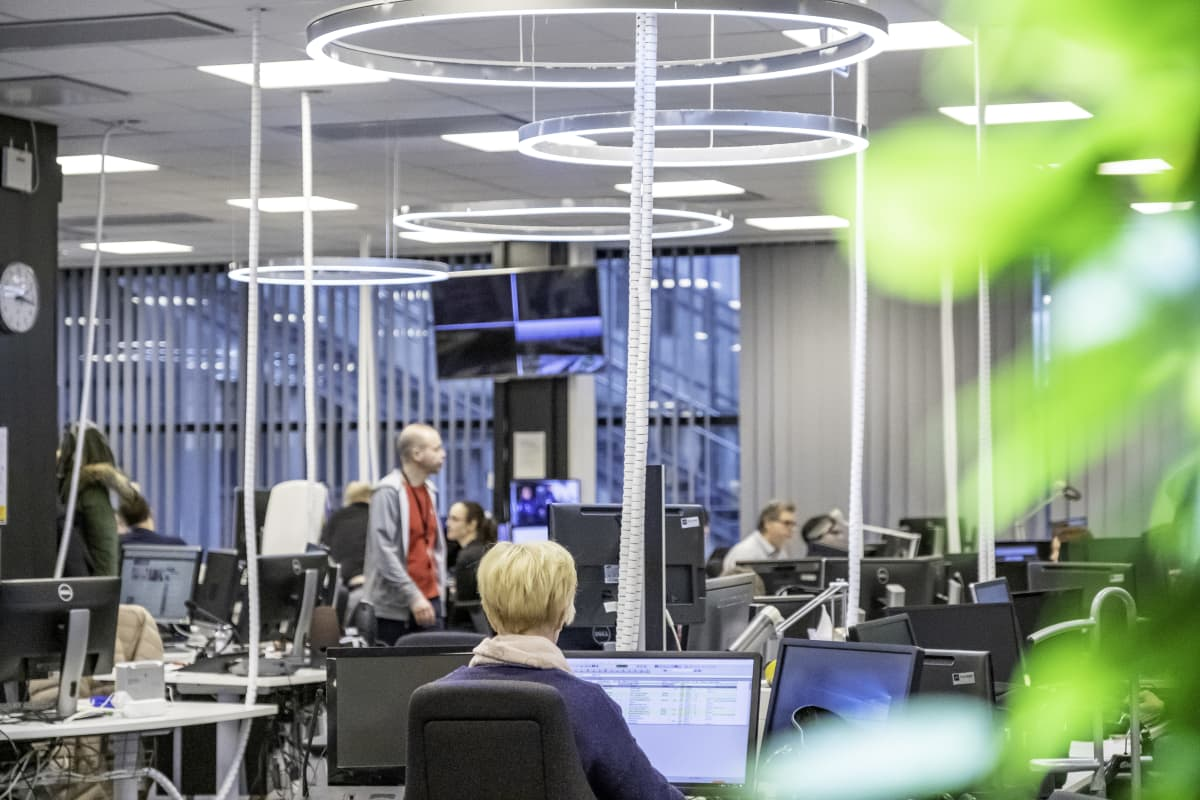 Kuva Ylen Uutisten avokonttorista, työntekijöitä työpisteillään.