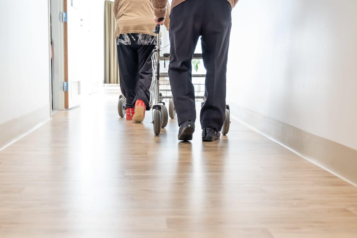 Kaksi vanhusta kävelee rollaattorien kanssa vanhustenkeskuksessa.