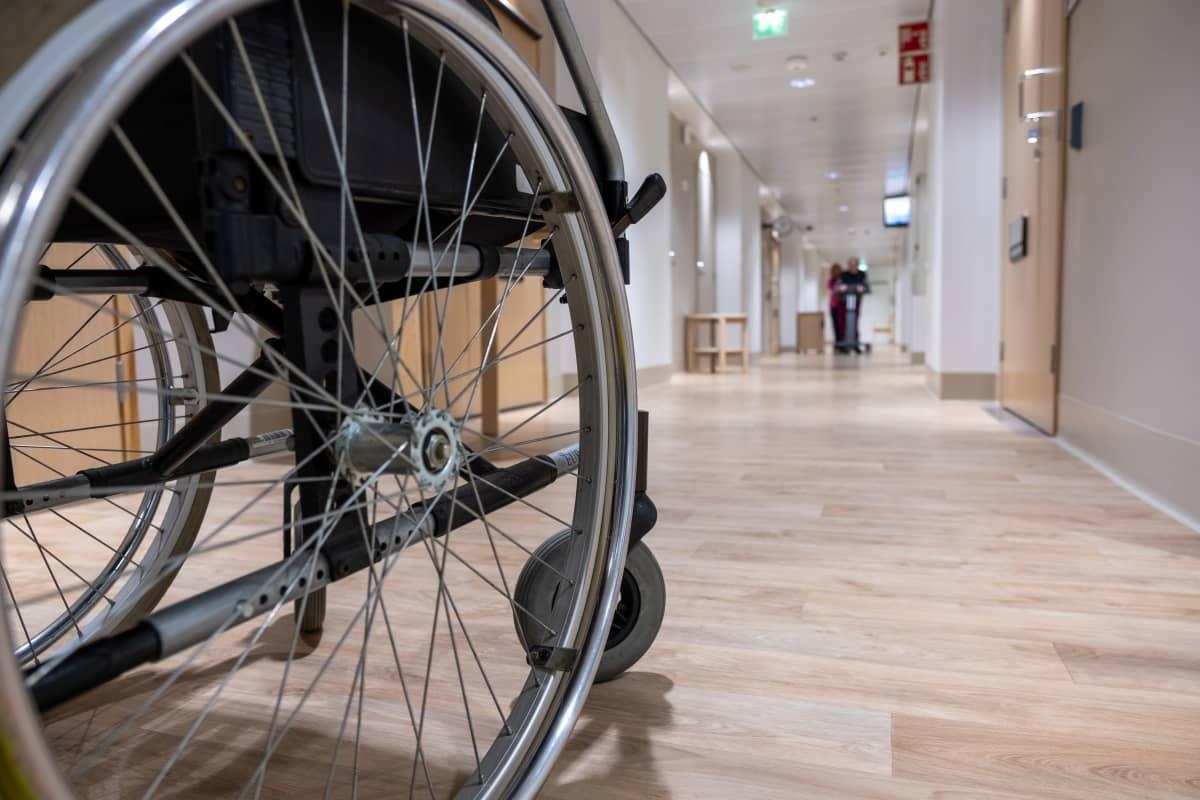 Fysioterapeutti avustaa vanhusta kävelyharjoituksessa Myyrmäen vanhustenkeskuksessa. Etualalla kuvassa pyörätuoli.