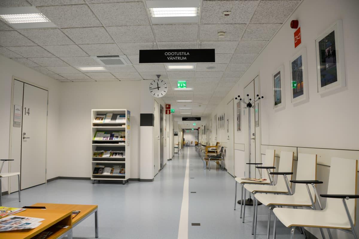En tom korridor i en hälsocentral. I taker finns en skylt där det står väntrum.