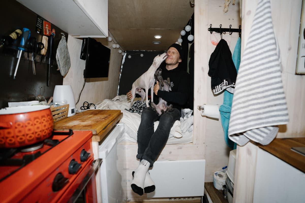 Samuli Hiltunen istuu pakettiautossaan sängyllä ja koira nuolee hänen naamaansa.