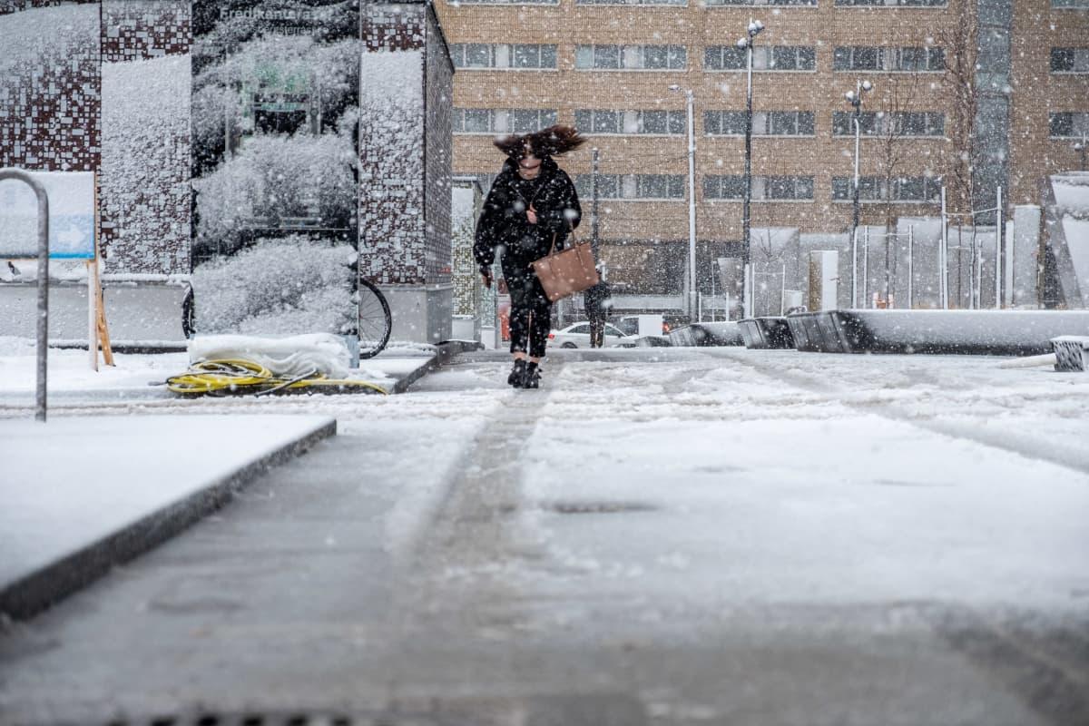 Henkilö kävelee lumisateessa Helsingissä.