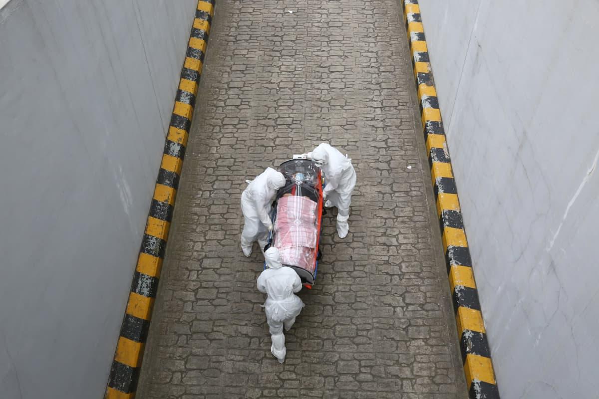Soulissa suojapukuihin pukeutuneet terveydenhuollon työntekijät siirtävät koronaviruksen saanutta potilasta ambulannista sairaalaan eristetyillä paareilla.