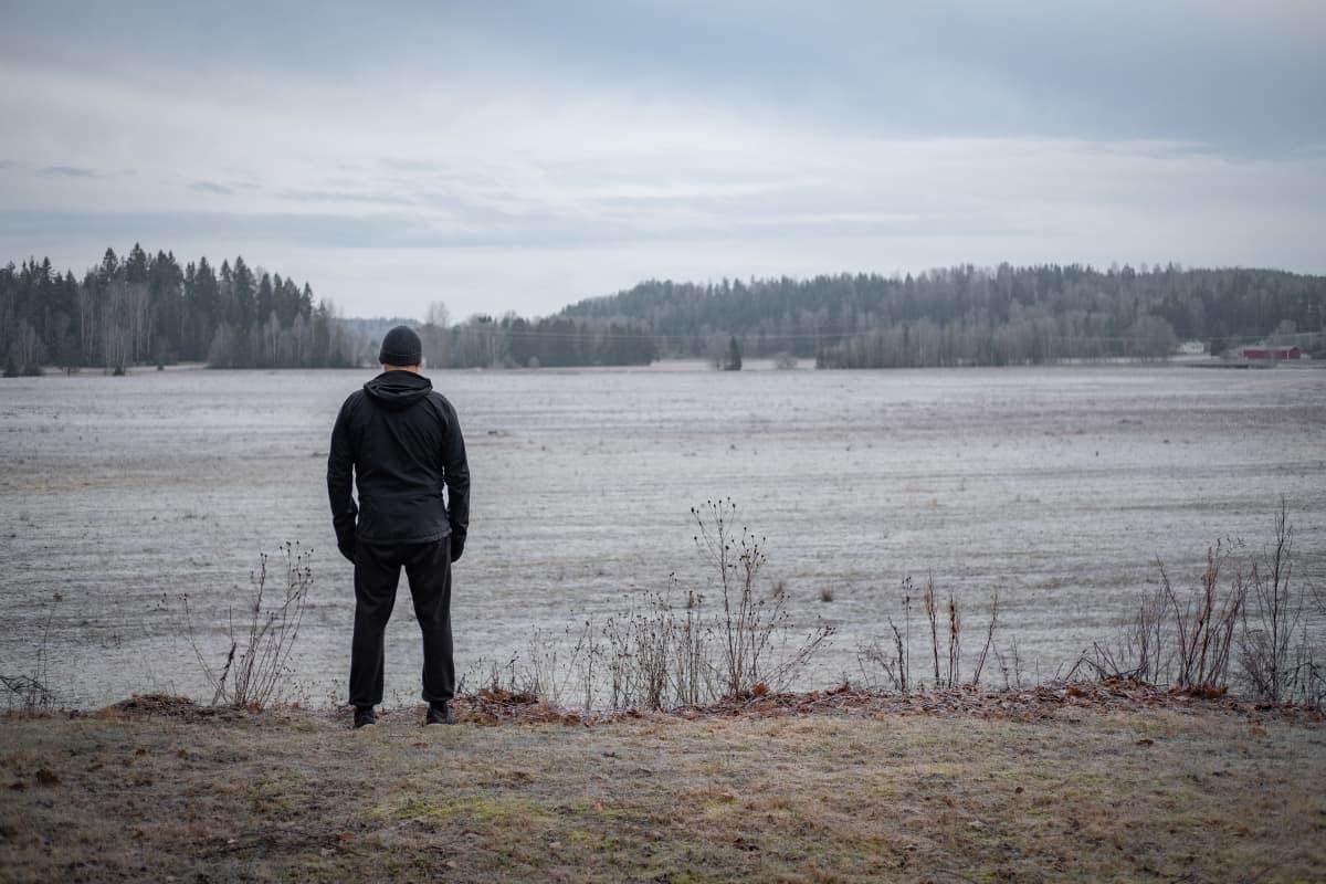Mies seisoo pellon laidalla selin kuvaajaan.