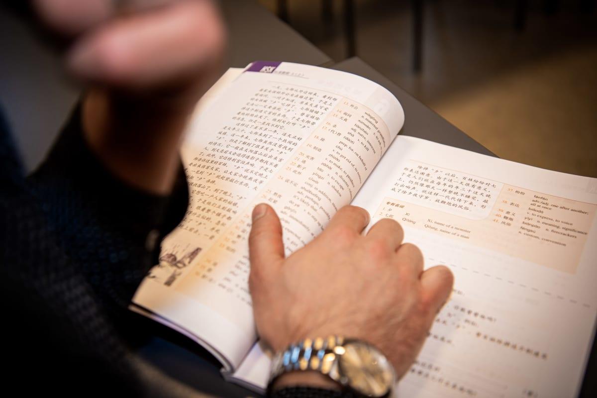 Konfutse-instituutissa mies selailee oppikirjaa.