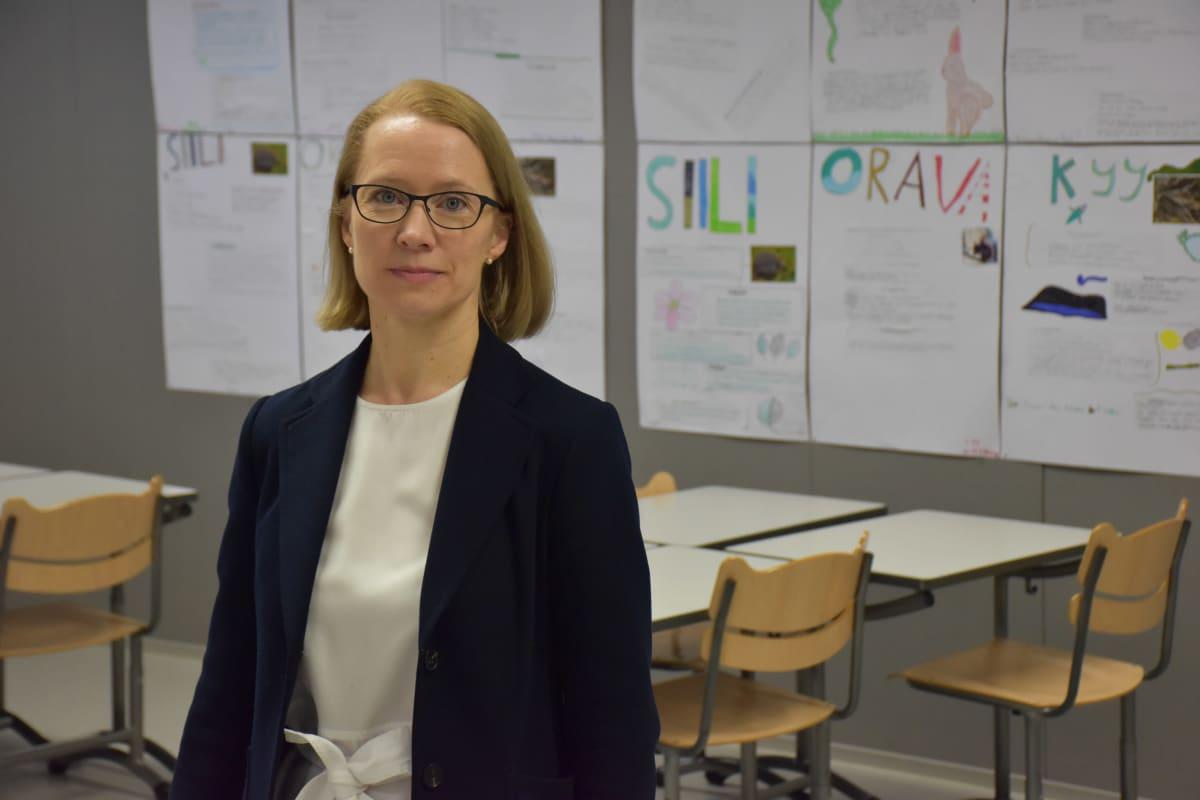 Sivistysjohtaja Eija Mattila seisoo tyhjässä luokassa.