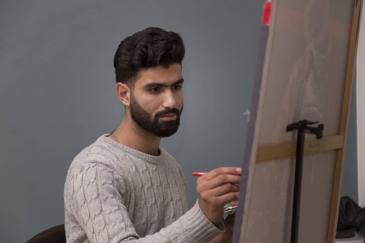 Ismail maalaa puolikuvassa.