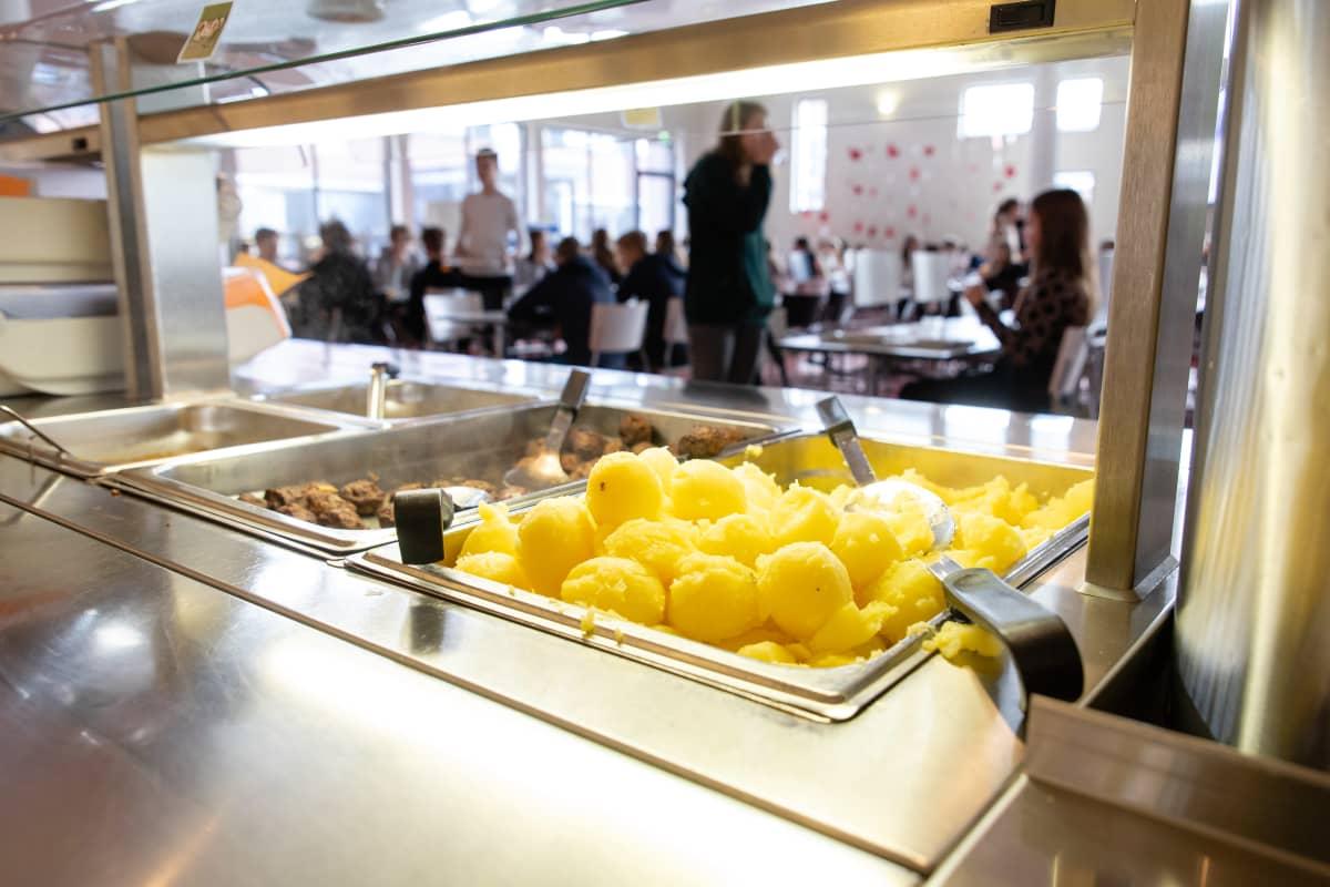 Oppilaita syömässä Kimpisen koulun ruokalassa, etualalla perunoita.