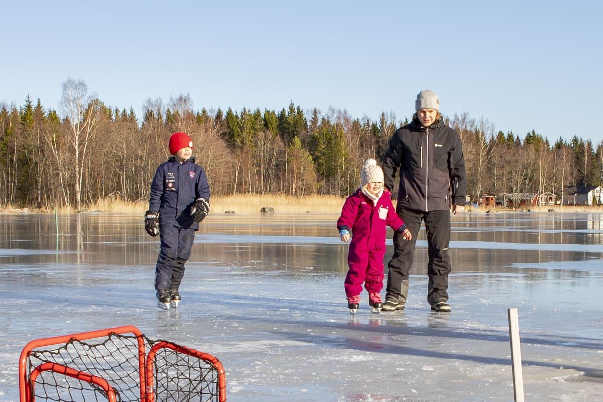 järven jäällä perhe luistelemassa