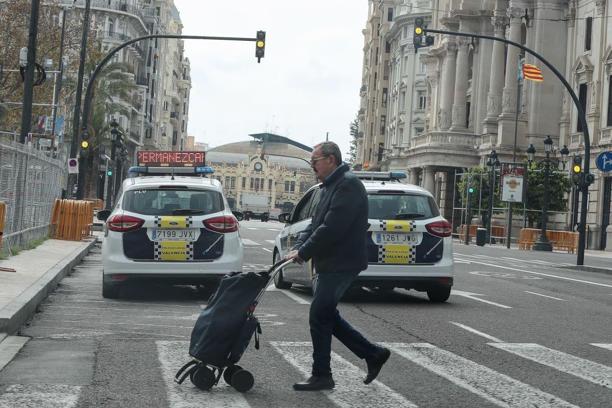 Mies kulkee suojatiellä vedettävän ostoslaukun kanssa. Muita ihmisiä ei näy, vain poliisiautoja.