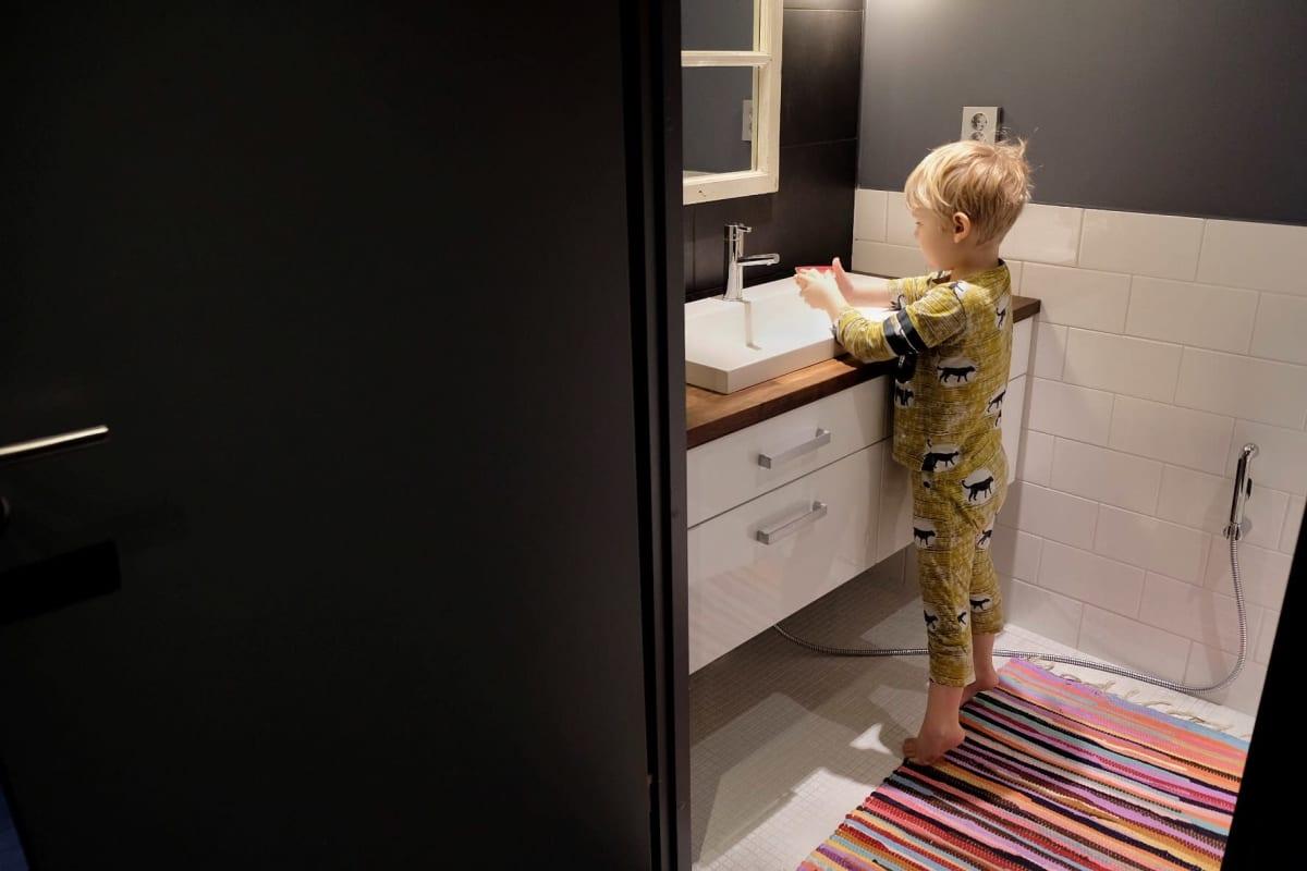 Lapsi pesee käsiään kylpyhuoneessa.