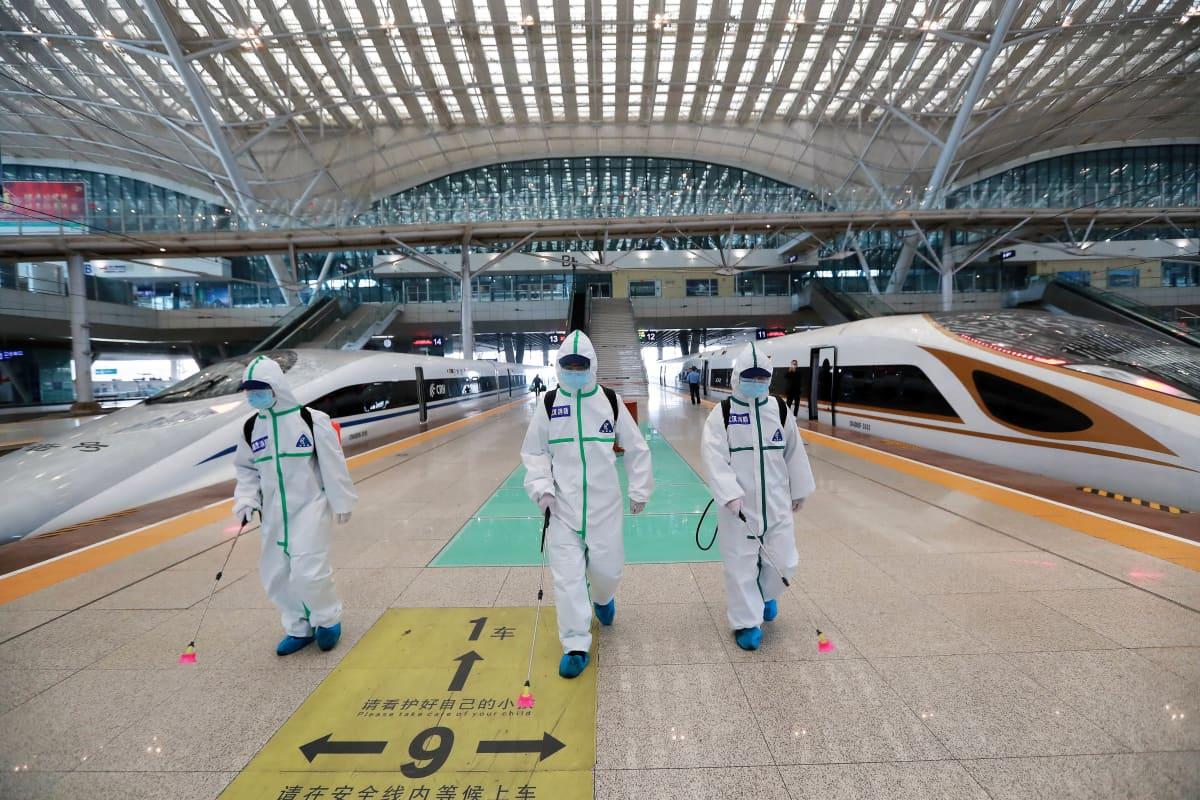 Kolme suoja-asuihin pukeutunutta työntekljää kulkee desinfiointiruiskujen kanssa laiturilla rautatieasemalla. Taustalla näkyy moderneja junia.