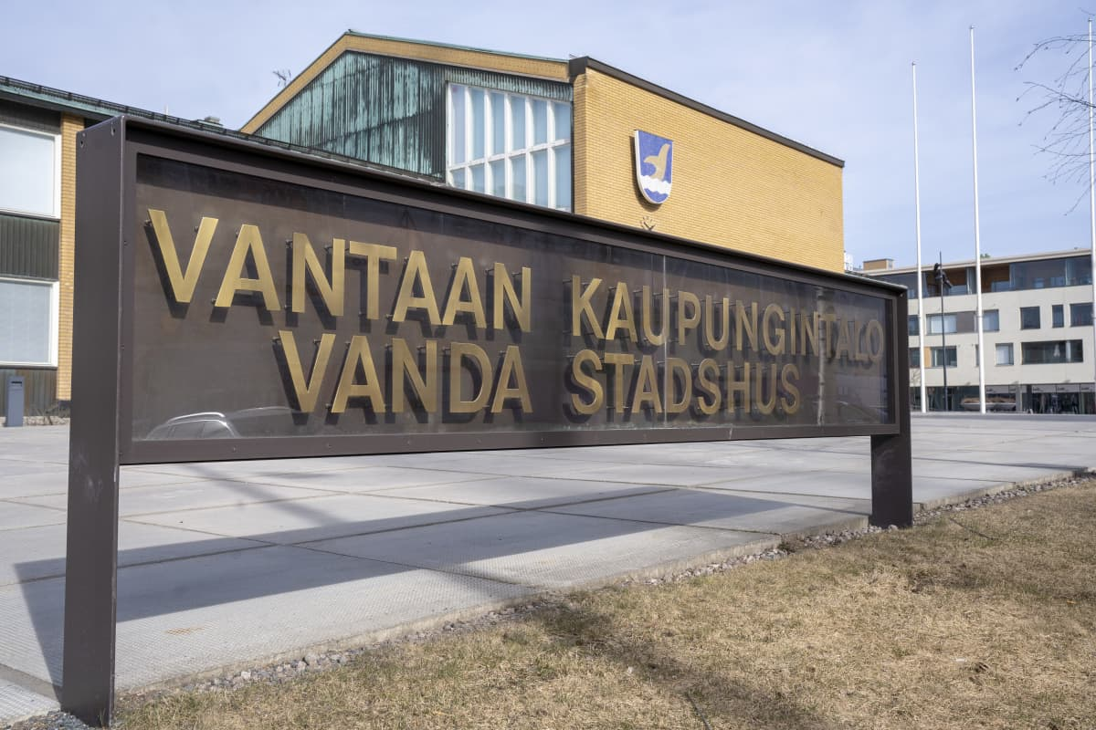 Kyltti jossa lukee Vantaan kaupungintalo. Takana näkyy kaupungintalo jonka seinällä on Vantaan vaakuna.