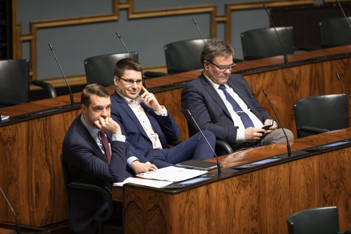 Tre riksdagsledamöter i rad i plenisalen. För nära, enligt coronabestämmelserna