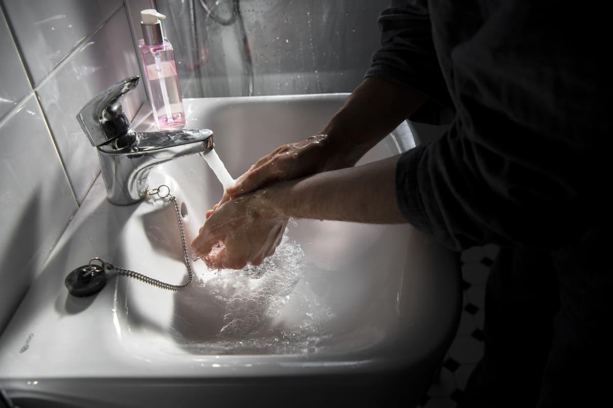 Mies pesee käsiään kylpyhuoneessa.