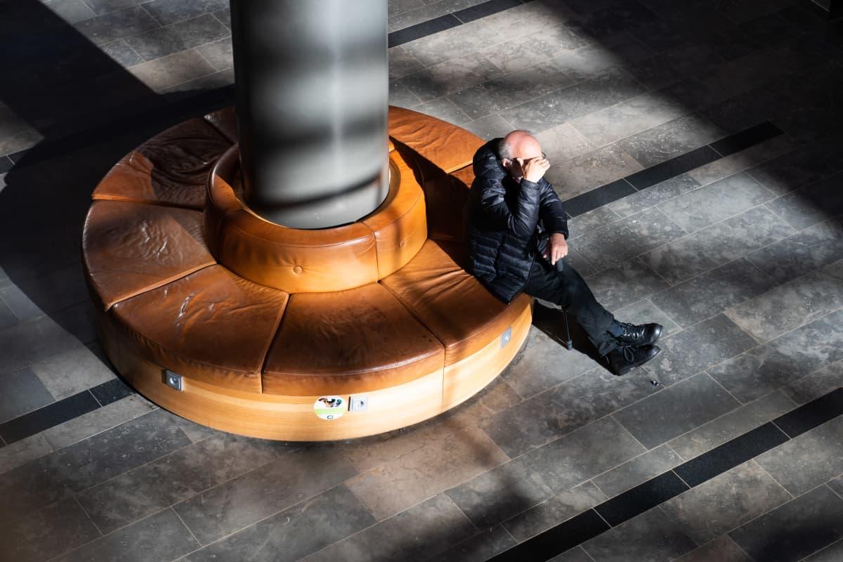 Eläkeikäinen mies istuu penkillä kauppakeskuksessa Espoossa.