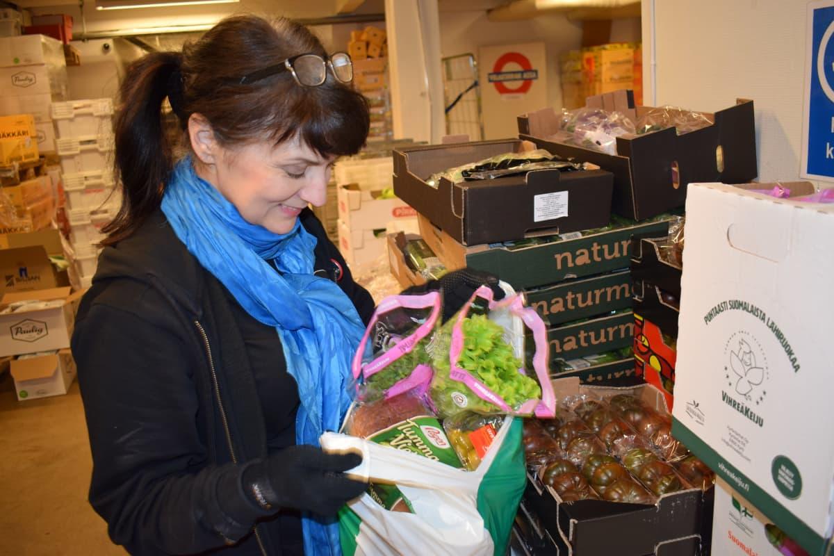 Vapaaehtoinen Maarit Helin katsoo ruokakassia.