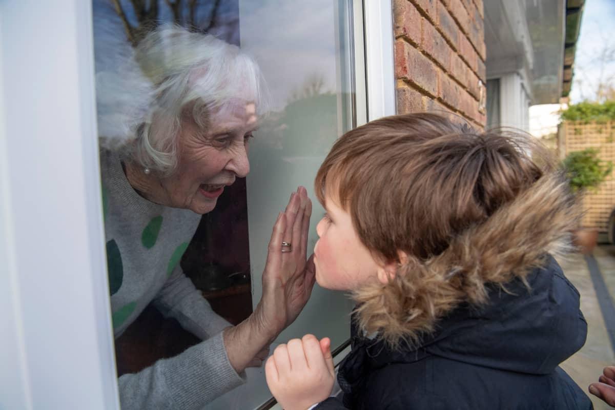 Lapsenlapsi tervehtii lasin läpi karanteenissa olevaa isoäitiään.