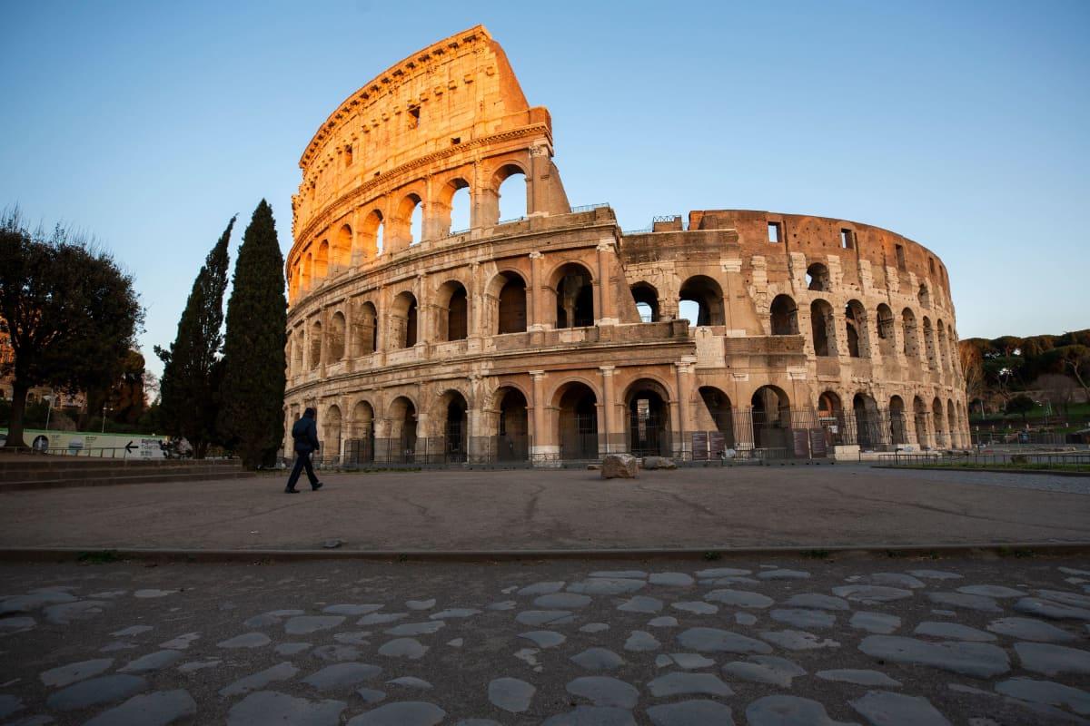Mies kävelyllä Colosseumin ohitse Roomassa, Italiassa 23. maaliskuuta 2020.