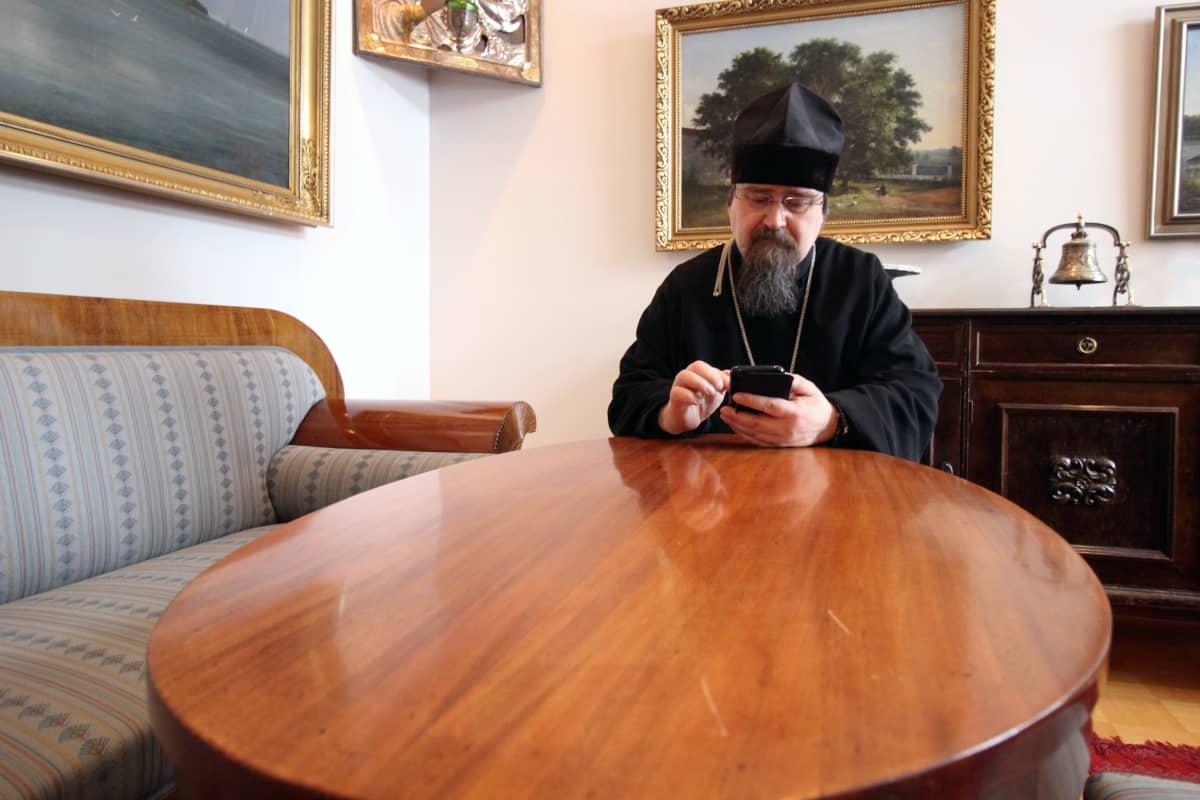 Arkkimandriitta Sergei lukee sähköposteja kännykältä työhuoneessaan.